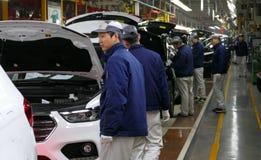 工作者在汽车工厂装配在装配线的一辆汽车 图库摄影