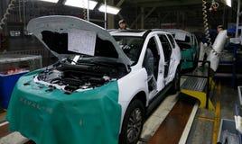 工作者在汽车工厂装配在装配线的一辆汽车 免版税图库摄影