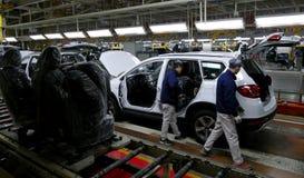 工作者在汽车工厂装配在装配线的一辆汽车 免版税库存图片