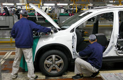 工作者在汽车工厂装配在装配线的一辆汽车 库存图片