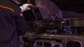 工作者在火车制造的一家工厂  工厂的工作者检查火车支架 工厂劳工 图库摄影