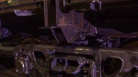 工作者在火车制造的一家工厂  工厂的工作者检查火车支架 工厂劳工 免版税图库摄影