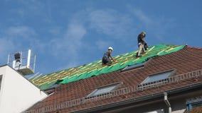 工作者在火以后修理屋顶 免版税图库摄影