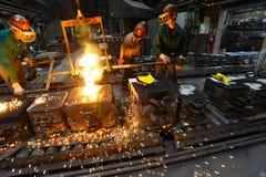 工作者在熔铸金属制件-工作安全的铸造厂和配合 免版税图库摄影