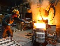 工作者在熔铸金属制件-工作安全的铸造厂和配合 库存图片