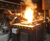 工作者在熔铸金属制件-工作安全的铸造厂和配合 库存照片