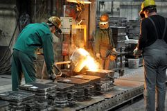 工作者在熔铸金属制件-工作安全的铸造厂和配合 免版税库存照片