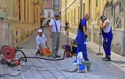 工作者在科希策,斯洛伐克铺在街道上的瓦片 库存图片