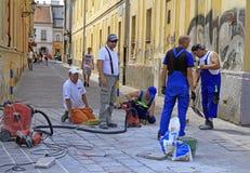 工作者在科希策,斯洛伐克铺在街道上的瓦片 免版税库存图片