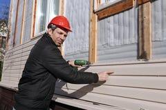 工作者在门面安装盘区米黄房屋板壁 图库摄影