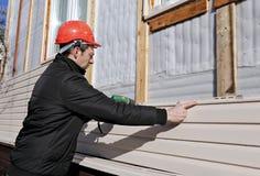 工作者在门面安装盘区米黄房屋板壁 免版税图库摄影