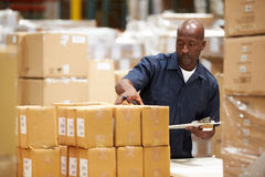 工作者在仓库里物品为急件做准备 免版税库存图片