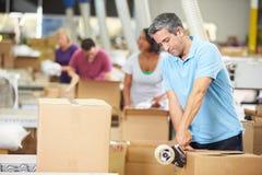 工作者在仓库里物品为急件做准备 免版税库存照片