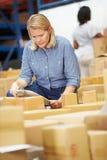 工作者在仓库里物品为急件做准备 库存图片