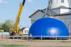 工作者在他的上帝的喀山母亲的被重建的教会屋顶准备安装圆顶在村庄Solodniki 免版税库存图片
