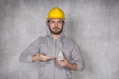 工作者在他的手上拿着一个房子 免版税库存图片