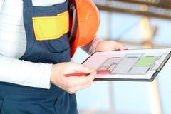 工作者在建造场所举行舱内甲板的项目 免版税库存照片