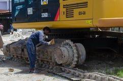工作者在建造场所清洗挖掘机 免版税图库摄影