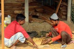 工作者在建造场所的锯切木头 库存图片