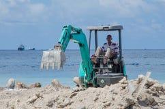 工作者在建造场所的骑马挖掘机 免版税库存图片