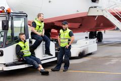 工作者坐拖车,当站立在跑道时的朋友 免版税库存图片