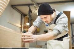 工作者处理木材加工机器的委员会 库存图片