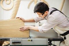工作者处理木材加工机器的委员会 免版税库存照片