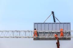 工作者安装在高速公路的大钢广告牌 免版税库存图片