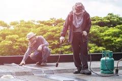 工作者安装沥青箔的小组在大厦屋顶  免版税库存图片