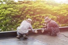 工作者安装沥青箔的小组在大厦屋顶  图库摄影