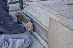 工作者安装陶瓷台阶瓦片 免版税库存图片