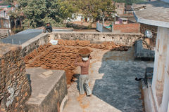 工作者带来在老房子屋顶的肥料  免版税库存照片