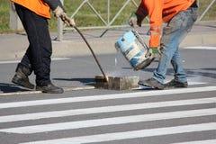 工作者应用一个路标于有白色油漆的行人交叉路斑马条纹行人穿越道并且洒条纹与稀土 库存图片