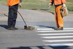 工作者应用一个路标于有白色油漆的行人交叉路斑马条纹行人穿越道并且洒条纹与稀土 库存照片