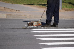 工作者应用一个路标于有白色油漆的行人交叉路斑马条纹行人穿越道并且洒条纹与稀土 免版税库存照片