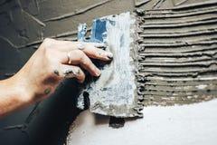 工作者应用在墙壁上的胶浆一块装饰砖的 库存照片