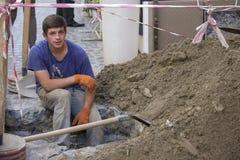 工作者开掘了修理的一个坑与水管一起使用 修理和替换日间下水道在深沟槽底部  库存照片
