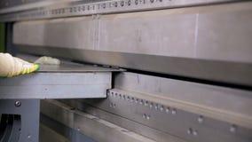 工作者手在工厂弯曲在一个现代弯曲的工业机器的金属板 股票录像