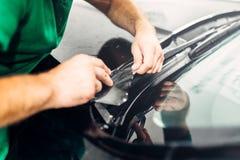 工作者手安装汽车油漆保护影片 免版税库存图片