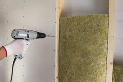 工作者手特写镜头有电螺丝刀紧固干式墙的对与绝缘材料矿物矿毛绝缘纤维职员的木木构架 免版税库存图片