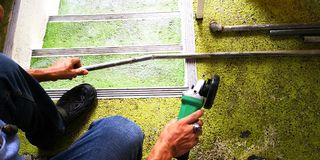 工作者打破了老铁管子,使用手钢剪的他 库存图片