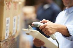 工作者扫描包裹在仓库里 免版税库存照片