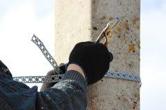 工作者把镀铬物钳位固定在垂悬的路标一个岗位 库存图片