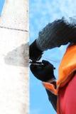 工作者把镀铬物钳位固定在垂悬的路标一个岗位 免版税图库摄影