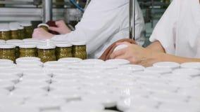 工作者抹一个玻璃瓶子与pesto调味汁在烙记前在传动机,特写镜头 股票视频