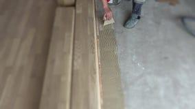 工作者抹上在水泥地板上的胶浆在新的公寓 地板放置 股票视频