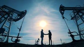 工作者握手在油田的 人们在运作的井架附近见面,握手 股票视频