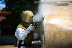 工作者是通过气压喷砂处理取消油漆 免版税库存图片