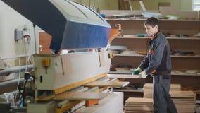 工作者木匠处理在机器的木家具零件在工厂 库存照片