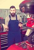 工作者检查一辆摩托车 免版税库存图片